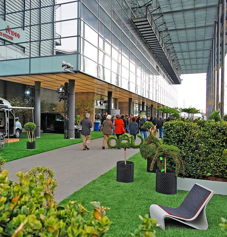 busy commercial walkway surrounded by artificial turf